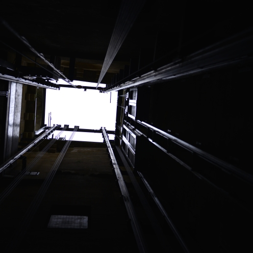 Looking up inside an open lift, itself inside a roofless bell-tower in Sarlat