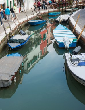The empty bottom third of the frame leads the eye in to this image of boats and flections on the island of Burano