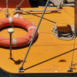 Detail from the deck of a small boat. The circle of the lifebelt is repeated by the coil of rope.
